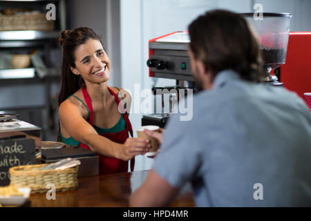 Smiling female staff serving cup of coffee to a customer at counter in shop - Stock Photo