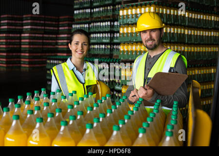Portrait of two factory workers monitoring cold drink bottles at drinks production factory - Stock Photo