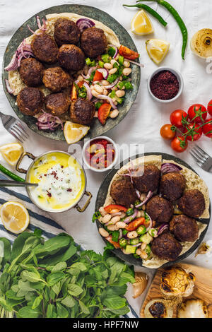 Turkish meatballs aka koftes served on pita bread on two copper plates with cold bean salad and red onions photographed - Stock Photo