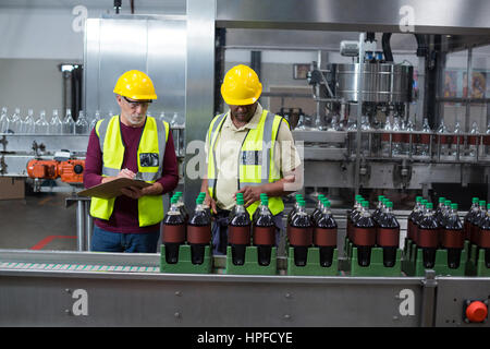 Two factory workers monitoring cold drink bottles at drinks production plant - Stock Photo