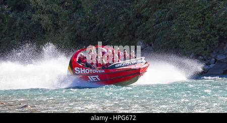 Queenstown, Otago, New Zealand. Shotover Jet boat speeding across the turquoise waters of the Shotover River. - Stock Photo