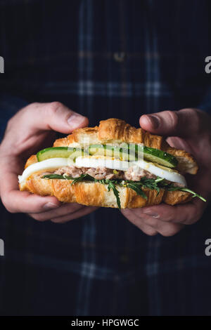 Hands holding tuna croissant sandwich with arugula, egg, tuna salad and cucumber. Closeup view, toned image - Stock Photo