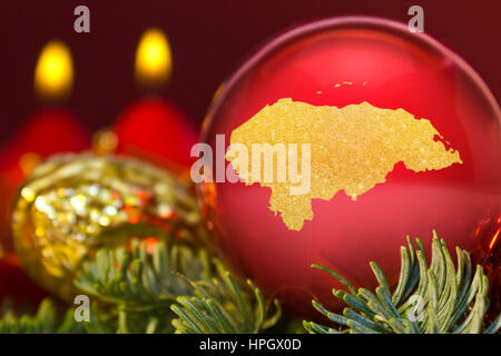 A glossy red bauble with the golden shape of Honduras.(series) - Stock Photo