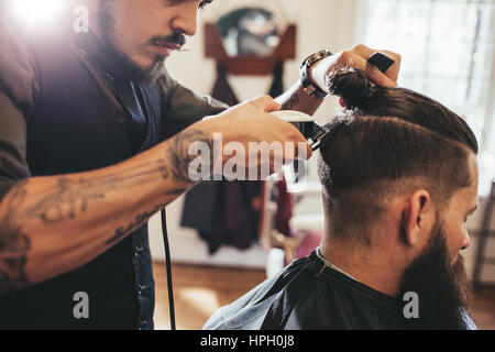 Close up shot of man getting trendy haircut at barber shop. Male hairstylist serving client, making haircut using - Stock Photo
