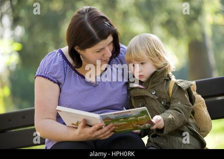 Model released , Mutter und Tochter, 3, sitzen auf einer Bank und betrachten ein Bilderbuch - mother and daughter - Stock Photo