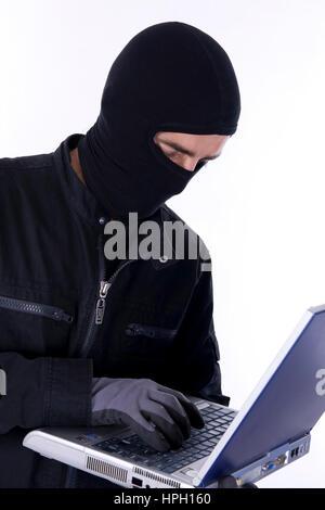 Model released , Symbolbild Datenklau, Einbrecher mit laptop - symbolic for data piracy - Stock Photo