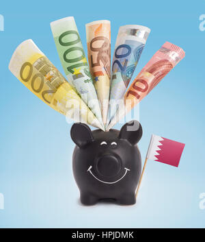 Ten,twenty,fifty,one hundred and a 200 Euro banknote in a smiling piggybank of Bahrain.(series) - Stock Photo