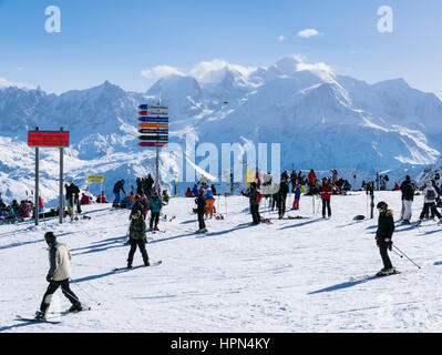 Skiers at Les Grandes Platieres in Le Grand Massif ski area with views to snowcapped Mont Blanc and mountains in - Stock Photo