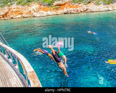 blue cruise yacht charter in turkey and greece, people dives into the sea, private group cruise along the mediterranean - Stock Photo