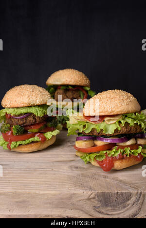 Juicy Hamburgers on sesame buns with succulent beef patties and fresh salad ingredients on a rustic wood table, - Stock Photo