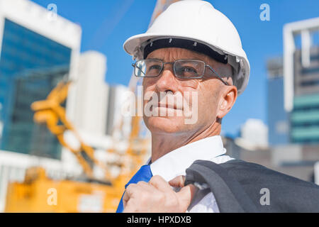 Confident construction engineer in hardhat and with jacket on shoulder - Stock Photo