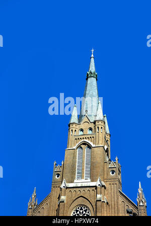 St. Joseph's Catholic Church in Greenville, Mississippi, stands tall against a clear blue sky. - Stock Photo