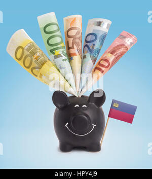 Ten,twenty,fifty,one hundred and a 200 Euro banknote in a smiling piggybank of Lichtenstein.(series) - Stock Photo