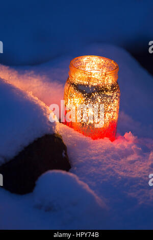 Decorative jar lanterns with candles glowing in snow - Stock Photo