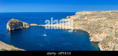 Gozo, Malta - Panoramic skyline view of Dwejra bay with Fungus Rock, Azure Window and sailboat on a nice hot summer - Stock Photo