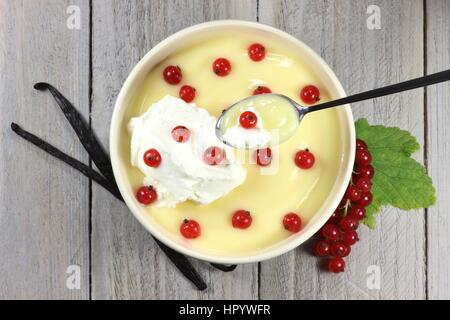 traditional Dutch custard served with red currants on wooden background - Stock Photo
