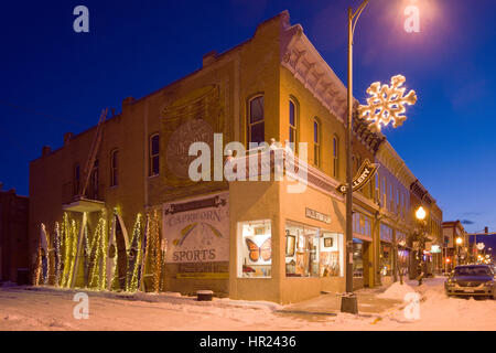 Dusk view of holiday lights illuminate colorful kayaks along a historic building in downtown Salida, Colorado, USA. - Stock Photo