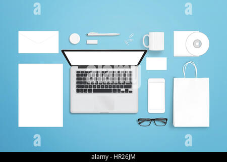 White blank stationery for branding presentation. Top view of blue desk with laptop, mobile phone, bag, paper, envelope, - Stock Photo
