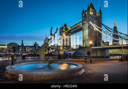 The lights come on at dusk on Tower Bridge on a calm but cold night in the capital city of London. - Stock Photo