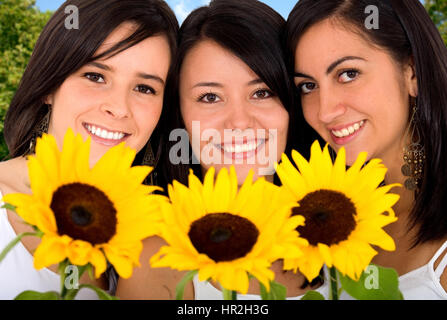 beautiful girls with yellow sun flowers smiling outdoors - Stock Photo