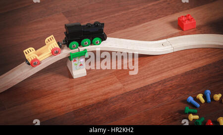 Toy train and wooden rails with bridge and colorful toys around - Stock Photo