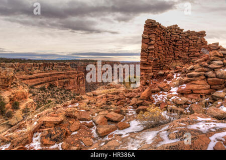 Snow-covered remnants of an Anasazi tower ruin on the rim of Mule Canyon in the Cedar Mesa area of Bears Ears National - Stock Photo