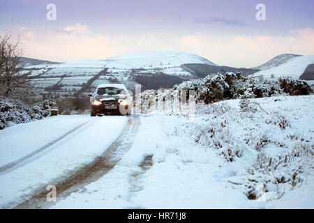 A car traveling down an isolated snow covered lane in rural Flintshire near to the village of Moel-y-Crio with the - Stock Photo