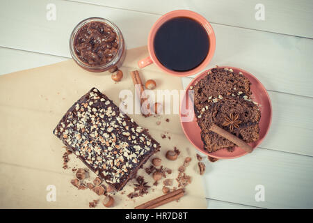 Vintage photo, Cup of black coffee and fresh baked gingerbread or dark cake with cocoa, chocolate and plum jam, - Stock Photo