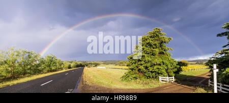 Rainbow over street next to vineyard in Tasmania, Australia - Stock Photo