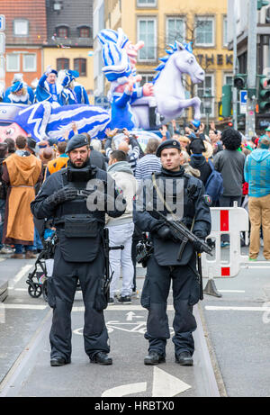 German Carnival parade in Düsseldorf, Police officers secure the parade, blocking roads with trucks, against terrorist - Stock Photo