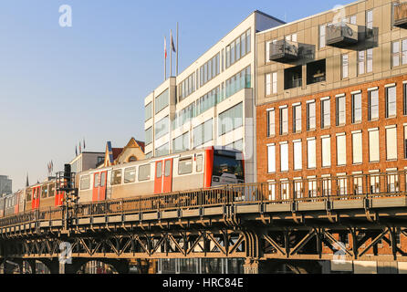 Hamburg, Germany - Februar 15, 2017: Subway train on a bridge in front of buildings near the station Baumwall. - Stock Photo