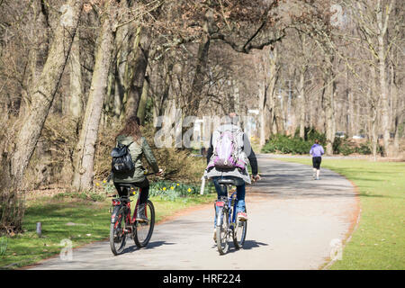 People cycling in a city park on a cold day. Tiergarten, Berlin, Germany - Stock Photo
