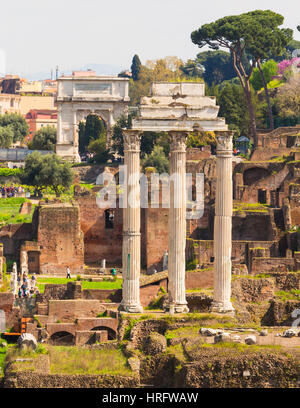 Rome, Italy.  The Roman Forum. The three columns of the Temple of Castor and Pollux.  The Arch of Titus in the background. - Stock Photo