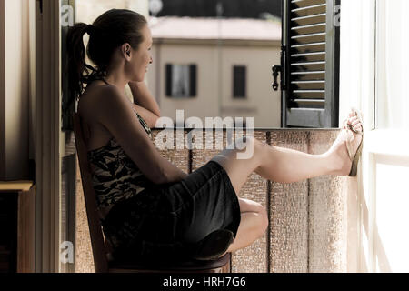 Model released, Junge Frau sitzt am Fenster - woman sitting front of a window - Stock Photo