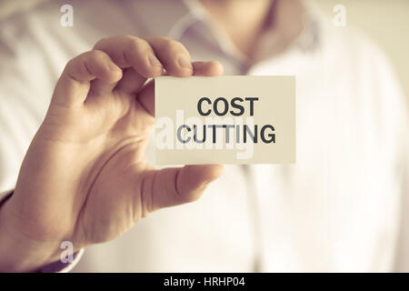 Closeup on businessman holding a card with text COST CUTTING, business concept image with soft focus background - Stock Photo