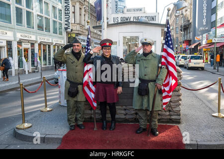Tourists posing with American soldiers at Checkpoint Charlie in Berlin, Germany - Stock Photo