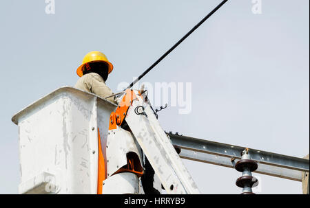 One technician is installing new wires of an electrical power line on hydraulic platform. - Stock Photo