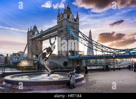A photographer takes a photograph of  'The  'Girl with a Dolphin' fountain as the sun sets behind Tower Bridge on - Stock Photo