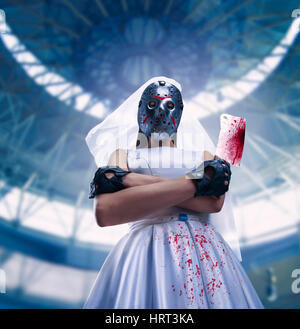 Serial murederer in wedding dress with bloody meat cleaver. Bride in hockey mask - Stock Photo