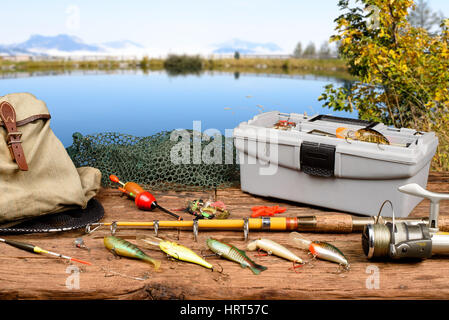 Fishing equipment on a wooden table with lake in background - Stock Photo