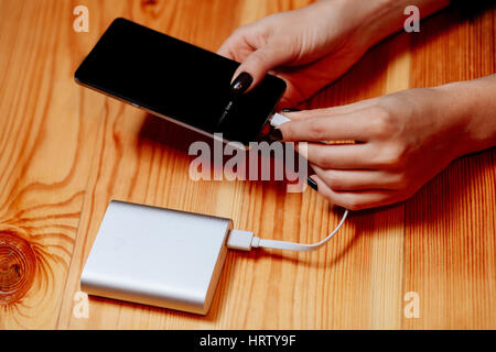 powerbank charging smartphone in hands close up on wood table - Stock Photo