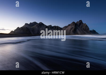 Stokksnes and Vestrahorn mountains viewed from the beach with waves in foreground, Iceland - Stock Photo