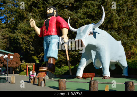 Family taking selfie with statues of Paul Bunyan and his ox Babe at Trees of Mystery in the Redwoods of northern - Stock Photo