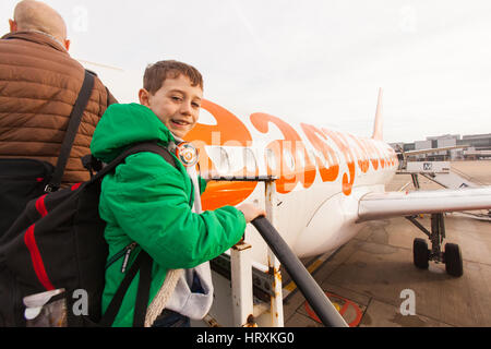 Seven year old boy excitedly boarding a Easyjet flight at London Gatwick airport. - Stock Photo