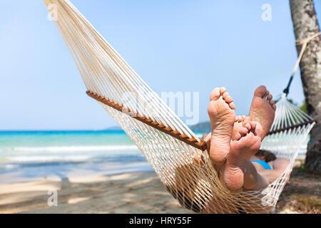 happy couple family in hammock on tropical paradise beach, island holidays, closeup of feet - Stock Photo