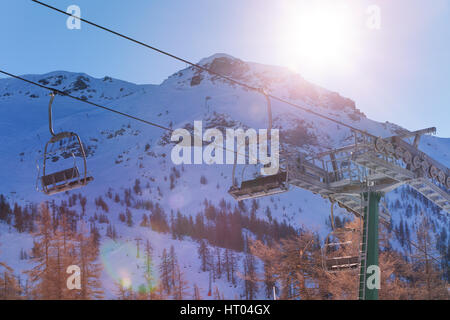 Beautiful mountain scene with empty chairlifts in the foreground at sunny day - Stock Photo