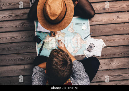 Man and woman making vacation plans using the world map. Couple sitting by the map and exploring it. - Stock Photo
