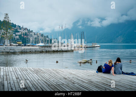 Two girls enjoy the tranquil waters of Lake Lugano, Switzerland. - Stock Photo