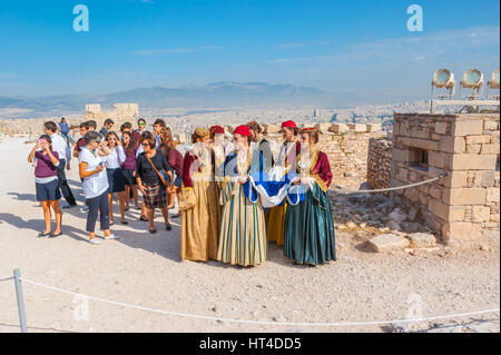 ATHENS, GREECE - OCTOBER 12, 2013: The traditionaly dressed women with National Flag of Greece on archaeological - Stock Photo