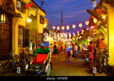 Locals and tourist in Tran Phu street at night, Hoi An, Vietnam - Stock Photo